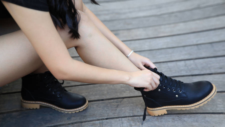 A woman trying on a pair of Dr Martens work boots