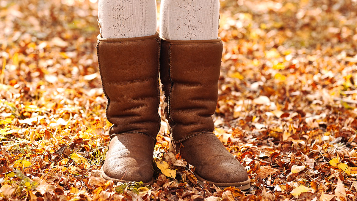 A woman wearing an UGG boots on an autumn forest