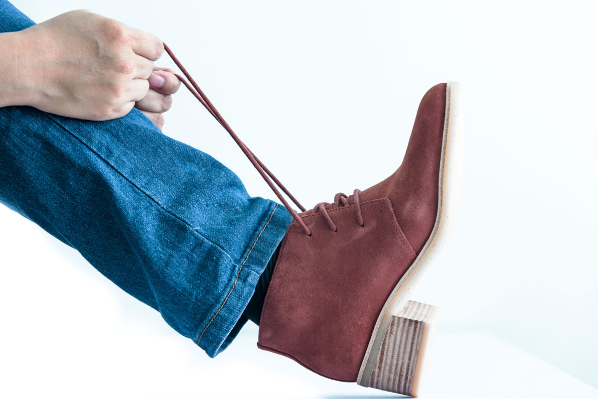 A brown leather boots being tied