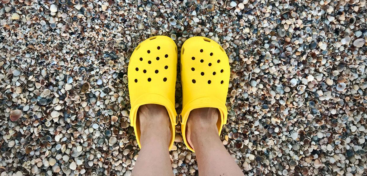 A bright yellow Crocs on a beach